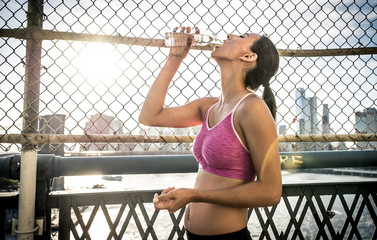 Female urban runner drinking some water after long run. Manhattan skyline background