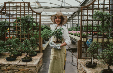 Photo sur Plexiglas Bonsai Bonsai greenhouse center. rows with small trees, woman working and taking care of the plants