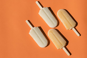 Varying  popsicles on an orange background. Flat lay of ice creams  in pop-art style with copy space. Horizontal  format