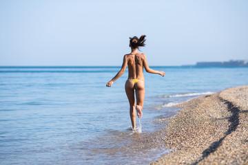 Barefoot female person running along seashore Wall mural
