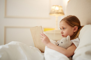 Cute little girl with teddybear lyiing in her bed and reading story tales before sleep