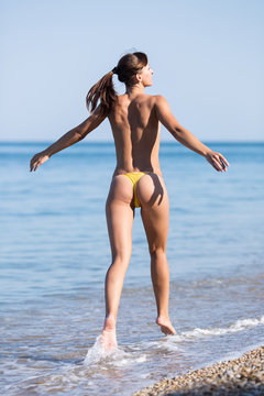 Girl in yellow swimming trunks running along seashore