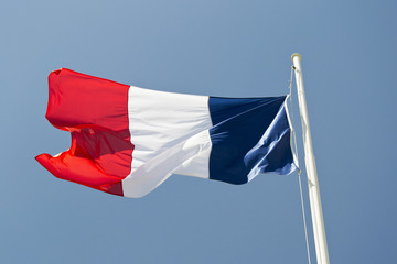 French flag waving in the wind with blue sky as background