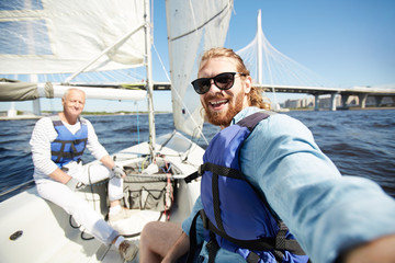Tuinposter Zeilen Happy young active man in sunglasses and lifejacket making selfie during sailing with senior friend
