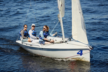 Spoed Foto op Canvas Zeilen Group of buddies in lifejackets sitting in yacht and sailing in the sea on vacation