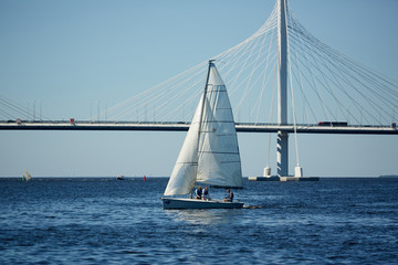 Group of humans in yacht sailing in large sea with bridge on background and blue sky above
