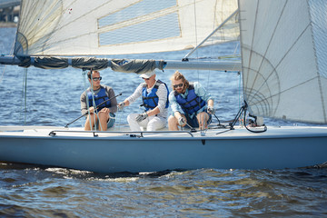 Group of active buddies in lifejackets sailing on yacht in open sea during summer voyage
