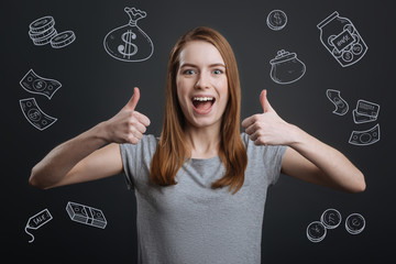 Rich person. Excited young woman putting her thumbs up and smiling happily after winning a big sum of money