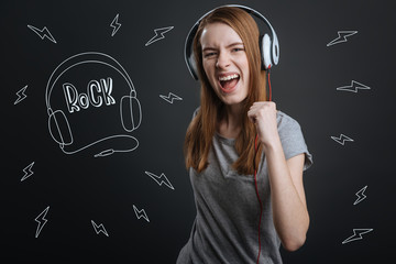 Rock music lover. Positive emotional girl wearing big headphones and feeling excited while listening to rock music with a help of them