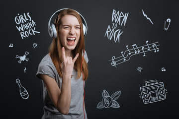 Born to rock. Emotional student looking excited and smiling while listening to rock music