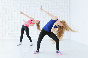 Group of two young women doing a fitness dance workout