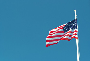 usa flag waving in the wind with blue sky as background