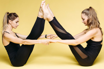 Two athletics girls in black sport wear doing yoga exercise.