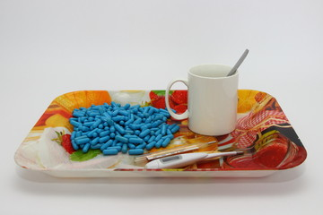 Cold, illness, treatment, autumn - a many blue capsules, pills next to a white mug with a spoon and two thermometers (digital and analog mercury) on a colored plastic tray