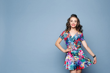Beautiful brunette woman in stylish floral dress holding its skirt with arm.