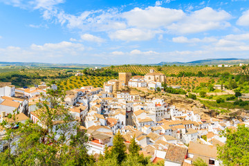 Church on hill top and white houses of Andalusian village during sunny day, Sentinel de las Bodegas, Spain