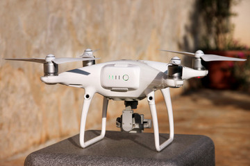 White quadcopter Drone with 4K digital camera on stand is ready for take off to fly in air to take photos, record footage from above. Drone with four motors, propellers, camera and red warning lights.