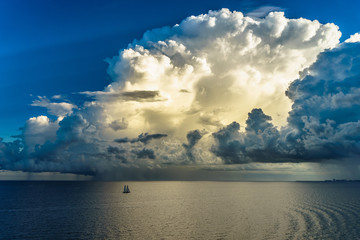 Sailing yacht in a stormy weather and huge cloud