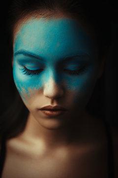 Beautiful asian girl is posing with creative blue makeup