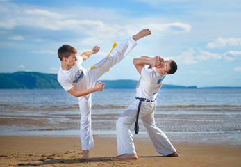The man is a coach of capoeira and a boy practicing capoeira on the beach. Man and young guy play staged fight.