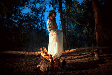 Woman in ethnic clothes with chaplet on a head near bonfire