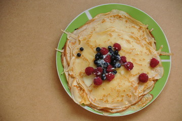 thin pancakes with raspberries, blueberries and condensed milk on a plate