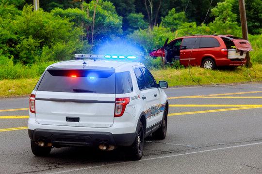 Police flashing blue lights at accident damaged car
