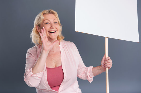 Join us. Pleasant middle-aged woman shouting slogans and holding a banner while posing isolated on a blue-grey background