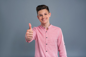 Pleased by everything. Upbeat teenage boy showing a thumbs up and grinning while posing isolated on a blue-grey background