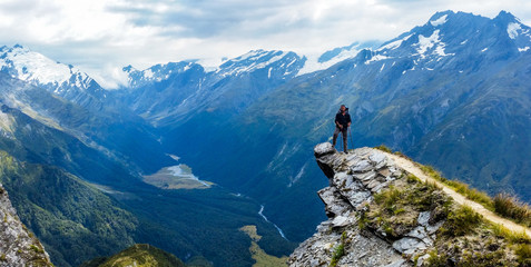 traveler standing at the edge of a cliff with a valley in the distance