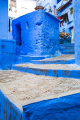 amazing stairs in between blue adobe buildings chefchaouen, morocco