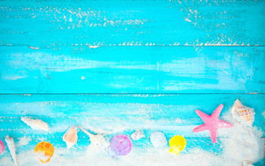 Beach background - starfish, shells, coral on wood table in blue sea color background. top view shot.