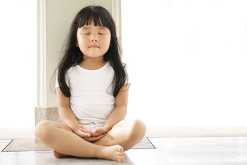 Asian children cute or kid girl sit for meditation with peace or quiet and relax in pavilion at temple or church and wearing white dress with sunlight on white background with space