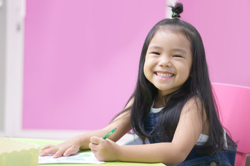 Asian children cute or kid girl happy smile and learning for coloring or paint on white paper and left hand with teacher or mother at kindergarten and nursery or school on colorful and pink background