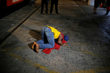 A migrant kisses the floor after arriving on a rescue boat at the port of Malaga