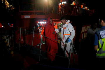 A migrant woman is helped by a rescuer on a rescue boat upon arrival at the port of Malaga