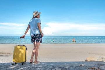 Young Asian woman with hat carrying suitcase at the beautiful sea beach in the weekend, travel concept.