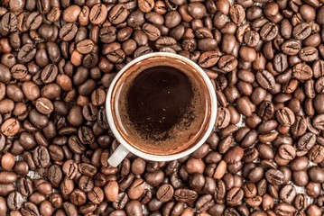 Fresh coffee surrounded by coffee beans