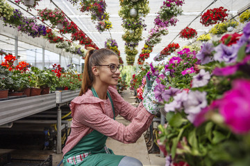 Young woman working on plants in garden full of flowers