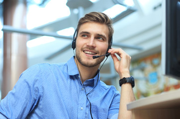 Smiling friendly handsome young male call centre operator.