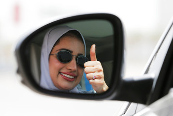 Zuhoor Assiri gestures as she drives her car in Dhahran