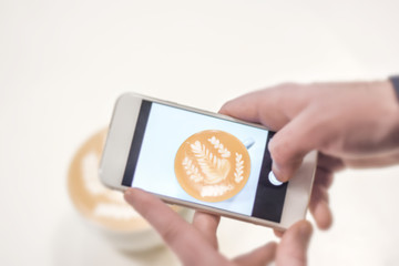 Mobile fotograph shoot of cafe latte on white table