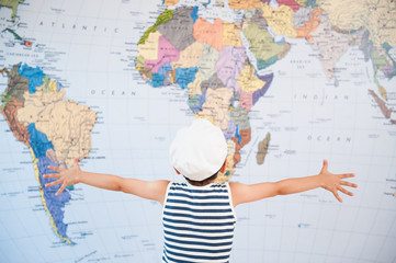 little child in captain hat spreading hands to world map before travel