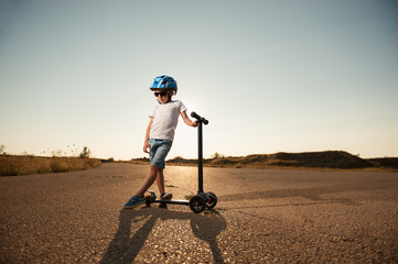 sad small kid in helmet and sunglasses with scooter on abandoned highway