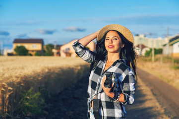 Young woman photographer with old camera on the open air