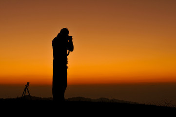 Silhouettes of Photographer with beautiful sky