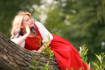 girl elf on a tree branch, in a red dress and a white blouse. resting bored