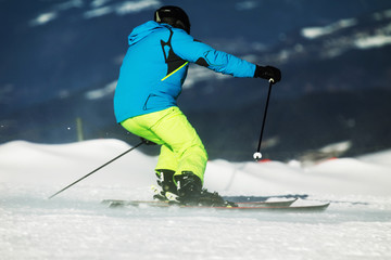 The skier in blue jacket and yellow spikes descends dynamically on the slopes