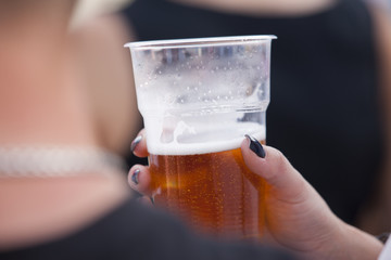 Beer in a plastic cup in a woman's hand