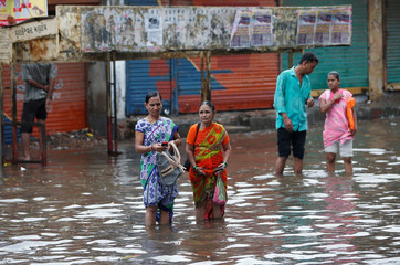 People wait for public transport at a flooded bus stop after heavy rains in Ahmedabad